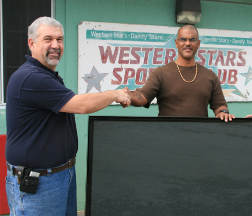 Wonderful gesture:  Ernie Terra of M&M International is greeted at the Western Stars Club this morning by its president Wayne Campbell. When the Sun told the retailer that the club's TV was broken, they were delighted to help. *Photo by Don Burgess