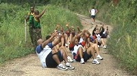 * Photo supplied. Working out: Players stop on their hike up a mountain to do sit ups.