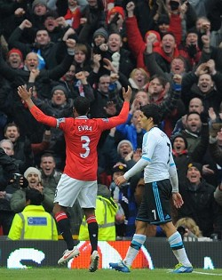 <strong>How sweet it is</strong>: Manchester United captain Patrice Evra celebrates a victory over Liverpool as Liverpool's Luis Suarez walks past him. Suarez refused to shake Evra's hand before the start of the match between the two clubs after serving an eight game ban for racially abusing Evra. <em>*AFP photo</em>