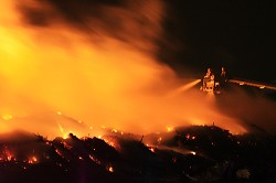 The scene at 1.45am Friday: two firefighters on an aerial ladder battle the<br />flames. <em>*Photo by Tony McWilliam<br /></em>
