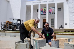 No flow: The water fountain in front of City Hall will be filled up with gravel and soil today, but City bosses say it is just a temporary measure. Ed Benevides is seen here, left, directing work at the fountains. <em>*Photo by Kageaki Smith</em>