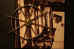 Looking back: The wheel of the Queen of Bermuda mounted on a picture of Captain Musson. <em>*Photo by Sarah Lagan</em>