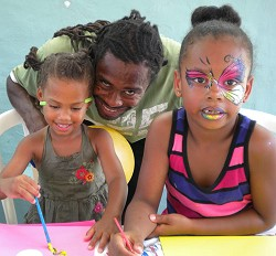 From left, Kenya Robinson, three, enjoys painting with her father Q Robinson and Maya Dean, seven.<em> *Photo by Amanda Dale</em>