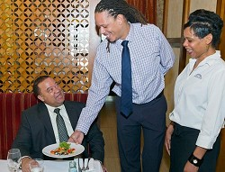 <strong>Service with a smile</strong>: Minister Furbert is served a sample of Victoria Grill's cuisine offering as part of Restaurant Week. Minister Furbert is being served by Victoria Grill's Assistant Manager Les Ruddock and Marjorie Whorms, server and bar tender. <em>*Photo supplied</em><br />