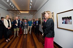 <strong>US Consulate General</strong> Grace Shelton introduces the exhibit. Behind her is a photo of herself alongside then-Premier Ewart Brown and his wife Wanda, former US President Bill Clinton and his Wife Hillary, Governer Sir Richard Gozney and Lady Gozney.<em> *Photo by Kageaki Smith</em>